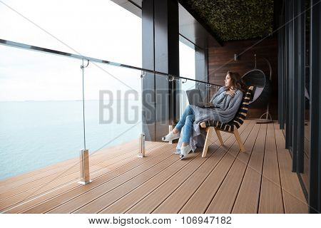 Sad serious beautiful young woman sitting wrapped in gray knitted coverlet on the big glass balcony