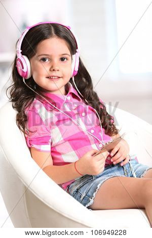 Attractive little girl sitting on comfortable chair and listening music with pink headphones in the room, close up