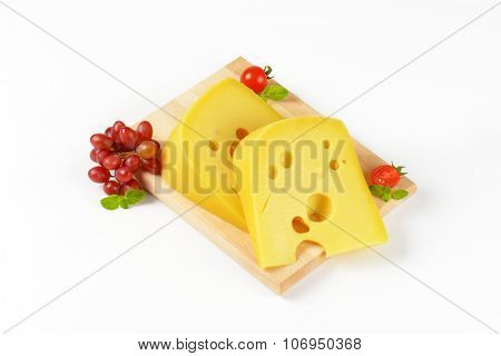 two wedges of fresh cheese with red grapes on wooden cutting board