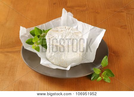 soft white rind cheese on brown plate