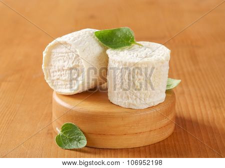 two soft white rind cheeses on wooden cutting board