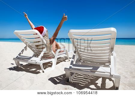 Happy Woman In Santa Helper Hat Lie On Sunbed Showing  Thumbs Up At The Beach