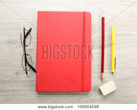 Workplace - red notebook and stationery on grey wooden background