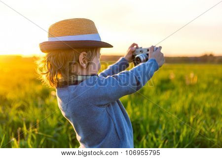 Little boy makes selfie outdoors