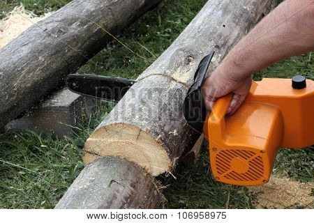 Worker Cuts A Beam By Electric Chain Saw