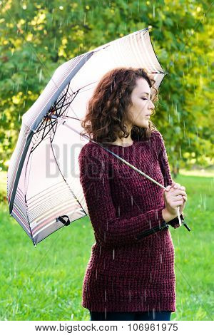 Young woman with umbrella at rainy day