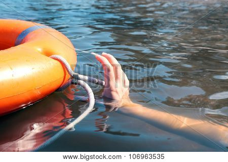 Hand trying to hold life buoy