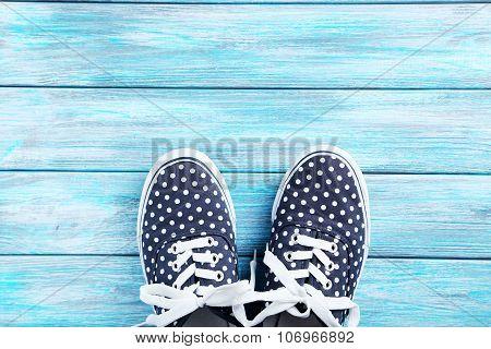 Female Gumshoes On Blue Wooden Background