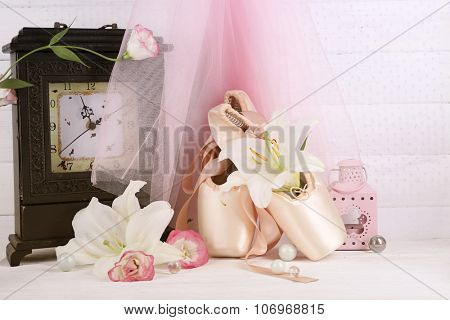 Beautiful composition of decorated ballet shoes on rosy satin background