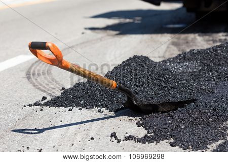 Shovel For Road Construction Works In A Heap Of New Asphalt