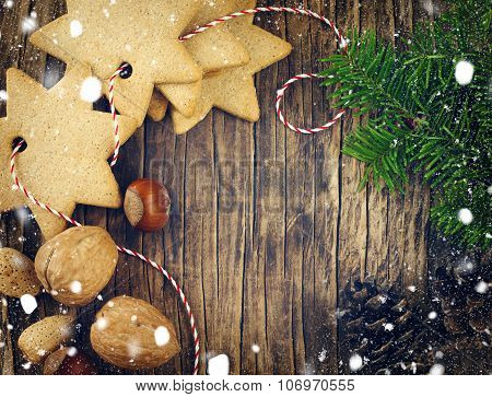 Christmas Cookies, Walnuts, Nuts, Pine Cones And Fir Branches On Wooden Background With Copy Space
