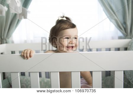 Infant baby resting and playing in his little baby bed