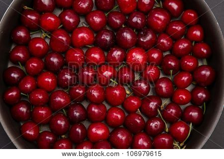 Top view of fresh red cherry in round baking tin
