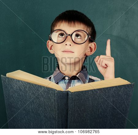 Schoolboy with book at the blackboard in classroom