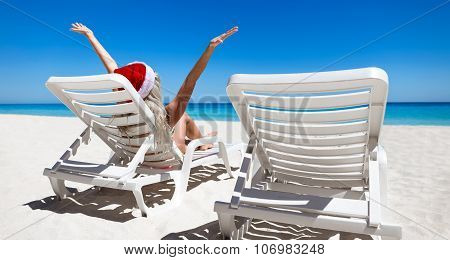 Happy Woman In Santa Helper Hat Sitting On Sunbed With Outstretched Hands At The Beach