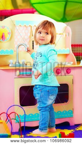 Cute Little Girl Playing With Toy Kitchen In Kindergarten