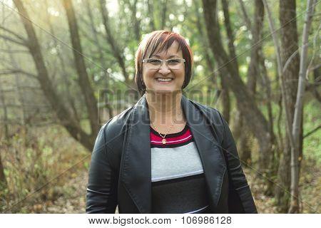 Portrait of elderly woman outside in forest