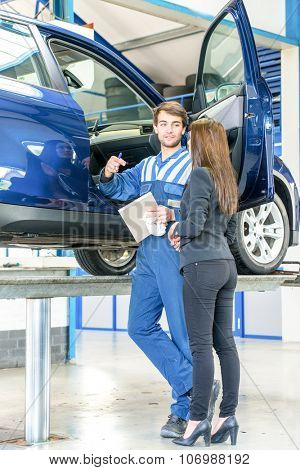 Mechanic discussing a quotation and maintenance fee to a young business woman whose car needs servicing in front of the open passengers door whilst the vehicle is on a car lift