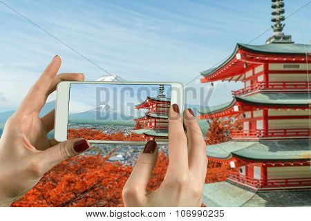 Back View Of A Woman Taking Photograph With A Smart Phone Camera At Mt. Fuji With Fall Colors In Jap