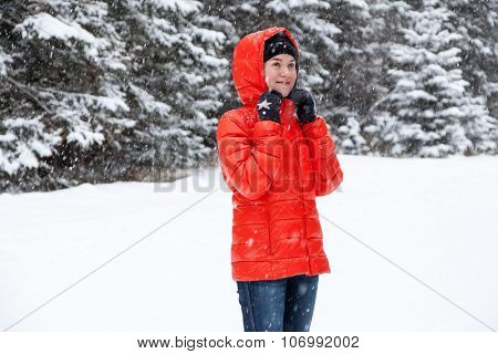 Pretty young woman playing snowballs in the mountains