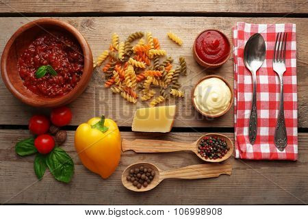 Pasta penne with tomatoes, sauce bolognese, cheese and basil on rustic wooden  background