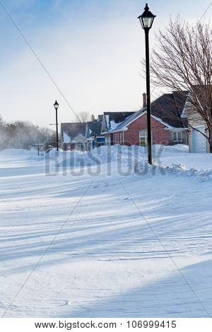 Wind blowing snow through a north American subdivision.