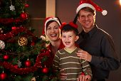 stock photo of nuclear family  - Happy family portrait parents with young boy smiling at christmas tree - JPG
