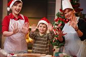 image of doughy  - Portrait of happy child with mom and grandmother at christmas baking raising doughy hands smiling - JPG