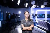Young beautiful brunette television announcer at studio standing next to the camera.TV director poster