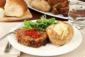 stock photo of baked potato  - Supper of meatloaf baked potato and fresh hot bread - JPG