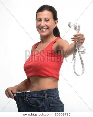Happy woman in old jeans pant after losing weight