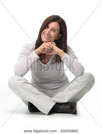 Isolated portrait of a beautiful smiling woman sitting on the floor with her legs crossed