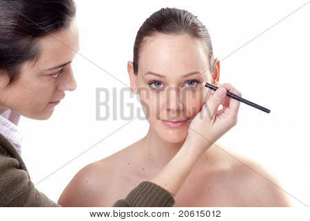 Portrait of attractive young adult woman applying eyeliner to a beautiful model