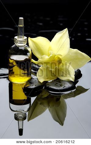 Spa still life with bottle of essential oil with orchid
