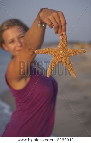 Cute Girl Is Holding Up An Seastar