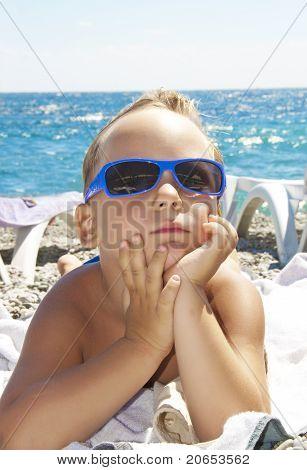 The Boy In A Sun Glasses Sunbathes On A Beach