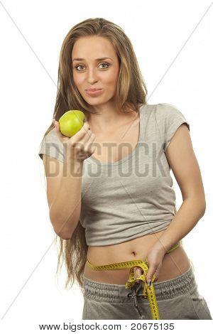 Closeup portrait of a charming woman masticating apple and measuring  her waist over white background