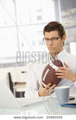 Determined businessman concentrating on work, thinking, sitting in office with football handheld.?