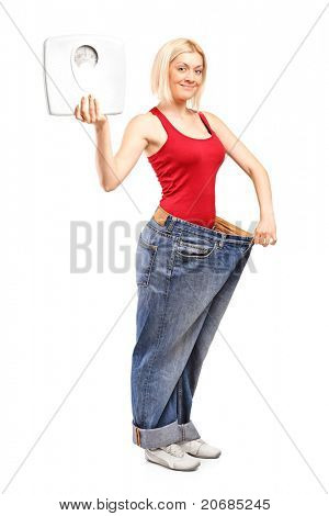 Full length portrait of a weight loss female holding a weight scale isolated on white background