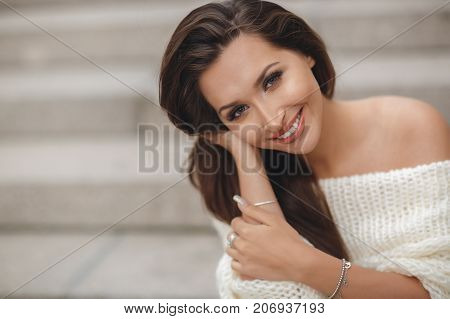 poster of Bright portrait of beautiful brunette woman with long straight hair,long eyelashes,grey eyes,light makeup,nice smile,white straight teeth,dressed in a beige Trouser suit, posing sitting outdoors on one of the streets in the spring