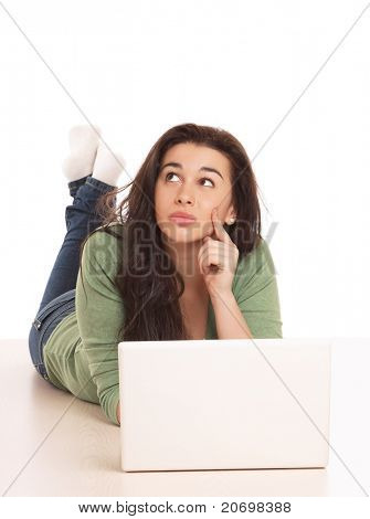 A thoughtful young girl with a laptop lying on the floor