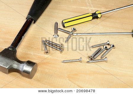 Hammer Screw-driver Screws On A  Board