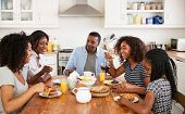 Family With Teenage Children Eating Breakfast In Kitchen poster
