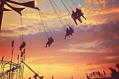 people riding rides and enjoying the summer atmosphere at a state fair at dusk toned with a retro vi poster