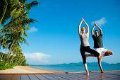 Постер, плакат: Привлекательная молодая женщина и мужчина делают йоги на причал с синий океан и еще один остров з