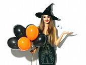 Halloween Party girl. Happy Halloween Sexy Witch holding black and orange Air balloons. Beautiful yo poster