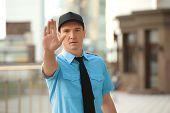 Male security guard showing stop gesture, outdoors poster