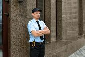 Male security guard near building, outdoors poster