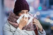 Pretty young woman blowing her nose with a tissue outdoor in winter. Young woman getting sick with f poster
