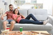 Young couple watching TV at home poster